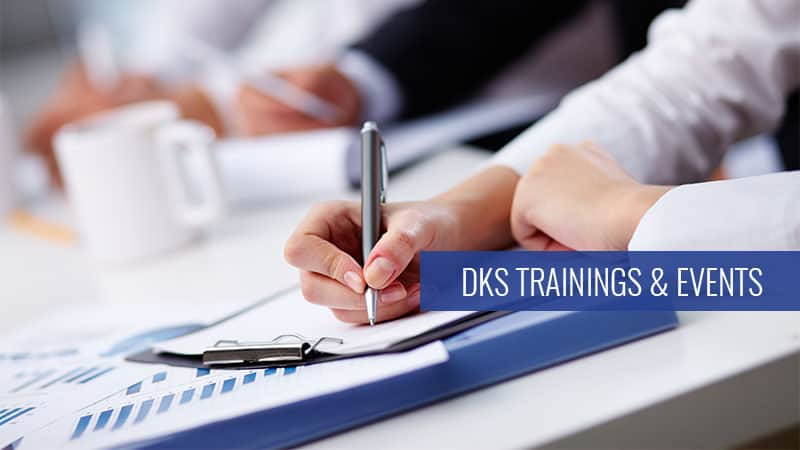 Right handed person taking notes with words DKS Trainings & Events